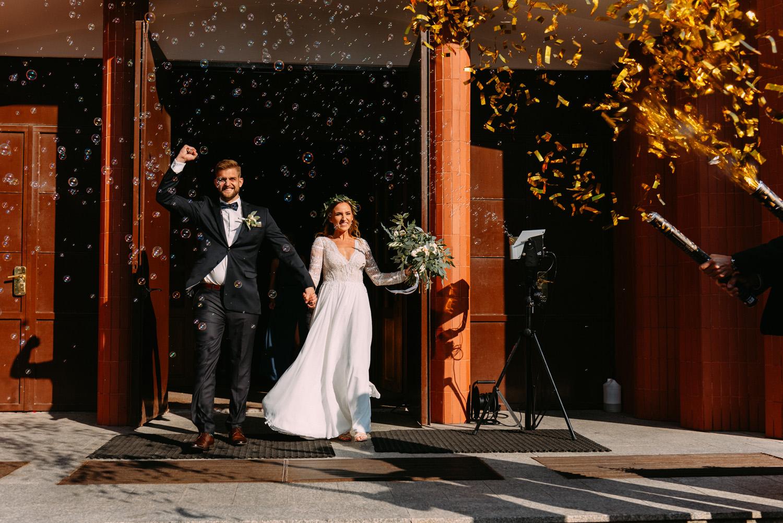rustykalny ślub- radosne wyjście młodej pary z kościoła w Warszawie- Luke Sezeck