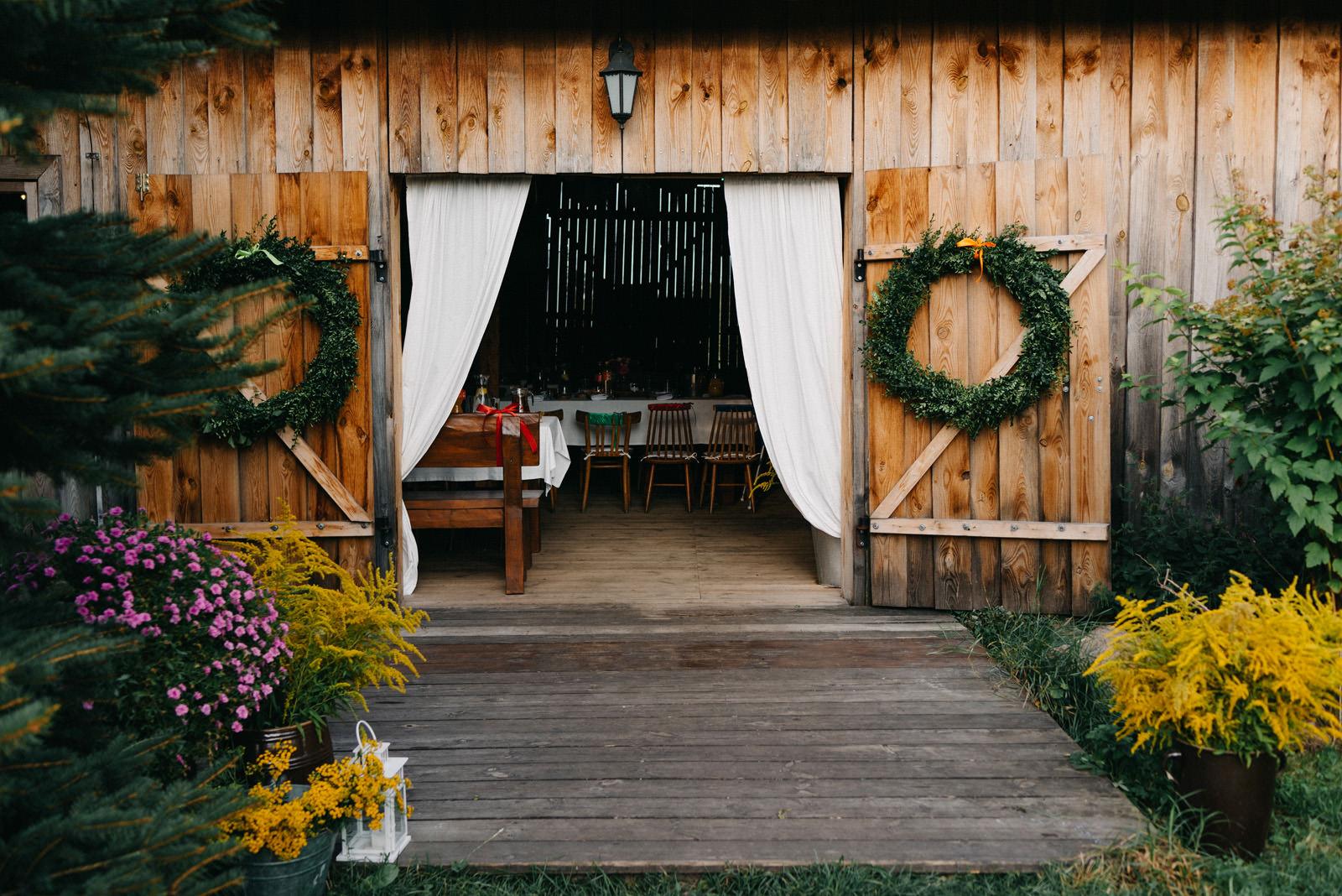 Osada młyńska - wejście do rustykalnej stodoły weselnej pod Warszawą - Luke Sezeck fotografia ślubna